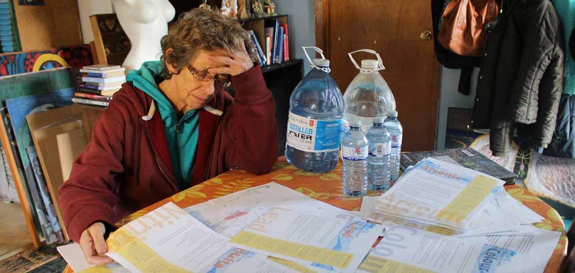 Marlene Brown reads water information sheets in Harrietsfield