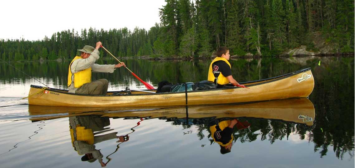 Paddlers canoeing on lake in Ontario